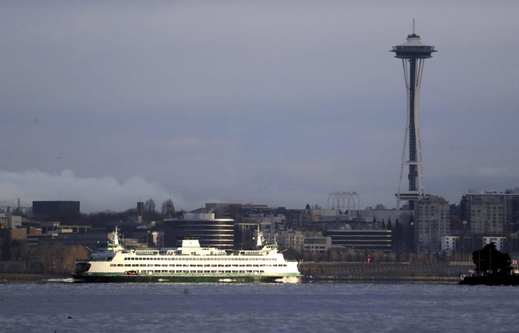 A Washington State ferry heading into Elliott Bay is illuminated by the sun as the city behind remains under clouds in Seattle in 2018.