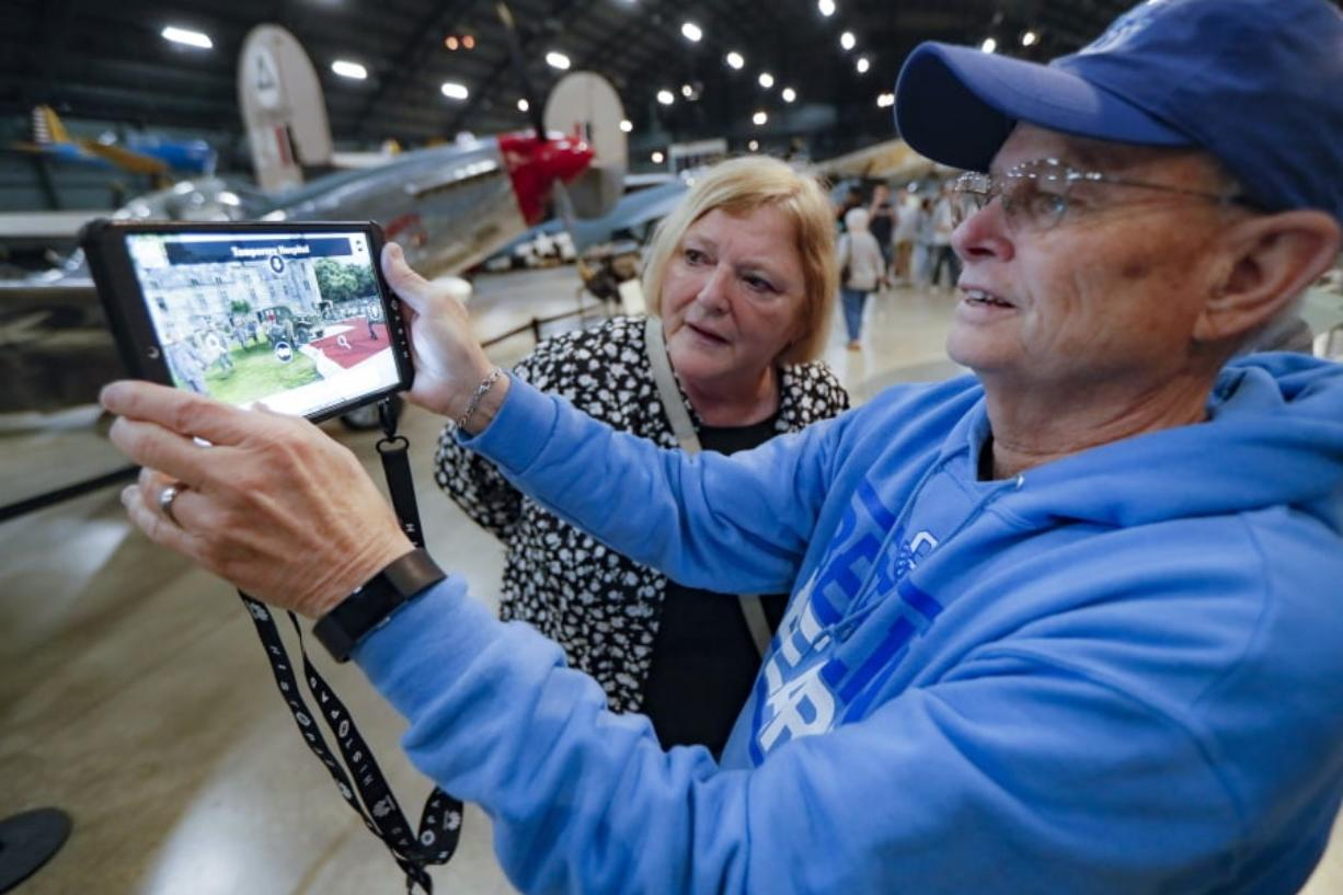 In this Friday, April 26, 2019 photo, Deane Sager, of Louisville, right, and his wife Cathy use a Histopad tablet to view scenes from operations on the western front of World War II at the The National Museum of the U.S. Air Force, in Dayton, Ohio. French-developed technology making its U.S. debut this month will allow new views of the D-Day invasion 75 years ago that began the liberation of France and helped end World War II. The National Museum of the U.S. Air Force near Dayton begins its D-Day commemorations May 13 with military-veteran paratroopers dropping from a vintage plane flying overhead, new exhibits and movies about the June 6, 1944, attack on heavily fortified German positions guarding the coastline.