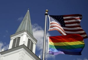 A gay pride rainbow flag flies along with the U.S. flag in front of the Asbury United Methodist Chur
