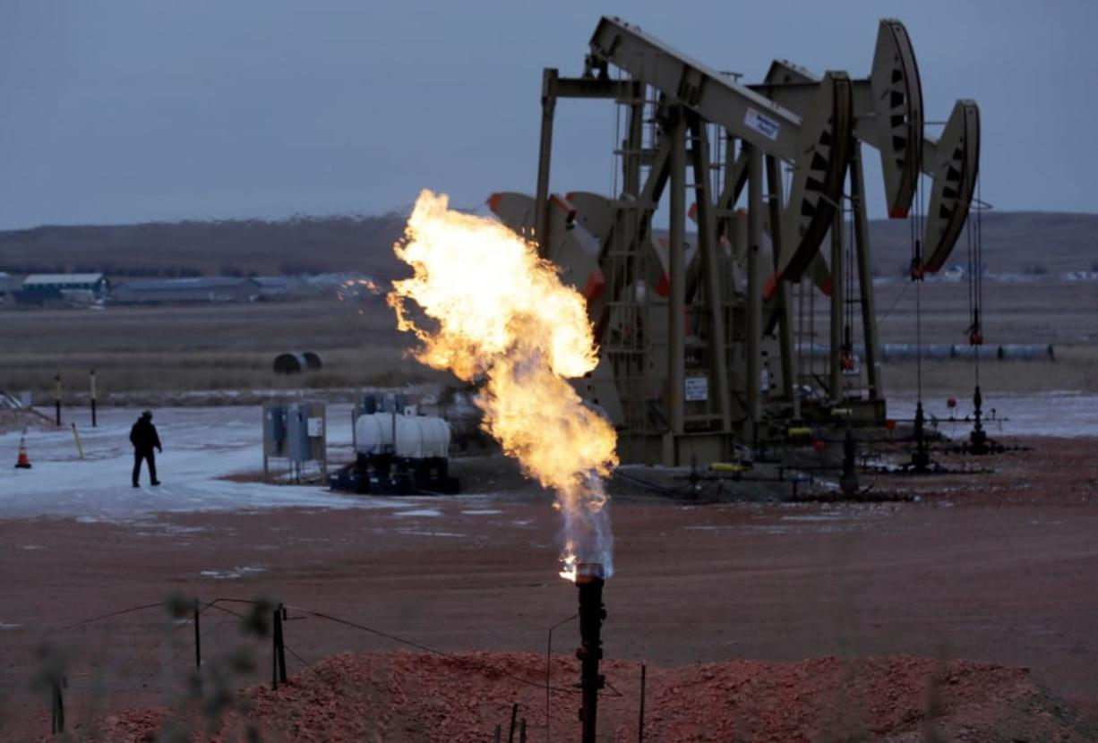 """FILE - In this Oct. 22, 2015 file photo, workers tend to oil pump jacks behind a natural gas flare near Watford City, N.D. Natural gas is being burned off and wasted at record levels in North Dakota because development of the pipelines and processing facilities needed to handle it has not kept pace. Natural gas production hit a record in March. But about 20 percent of it went up in flames through """"flaring,"""" the process of burning off the gas when it can't be captured. (AP Photo/Eric Gay, File)"""
