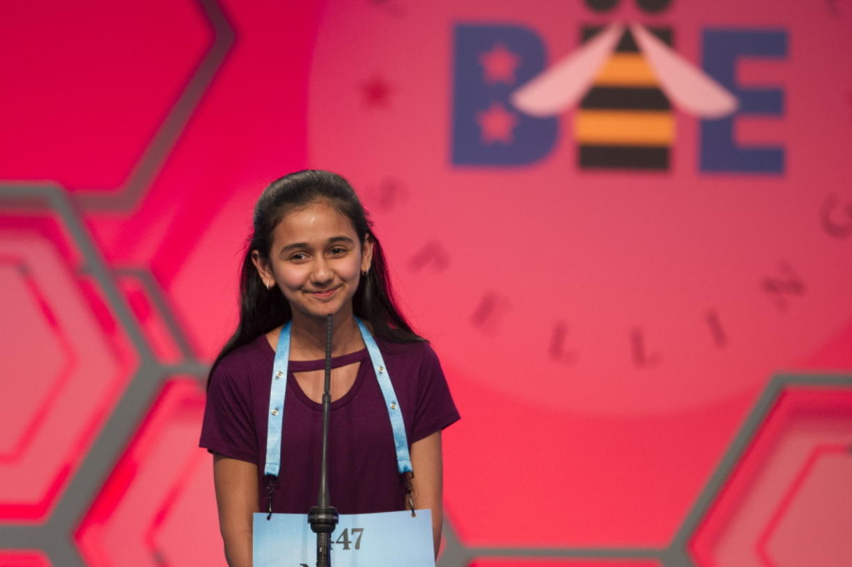 FILE - In this May 31, 2018, file photo, Naysa Modi, 12, from Frisco, Texas, spells her word incorrectly during the evening finals of the Scripps National Spelling Bee in Oxon Hill, Md. Ties are back at the Scripps National Spelling Bee. To the relief of many participants, bee organizers have gotten rid of the written test spellers took just in case a single champion couldn't be identified during the ESPN-televised finals.