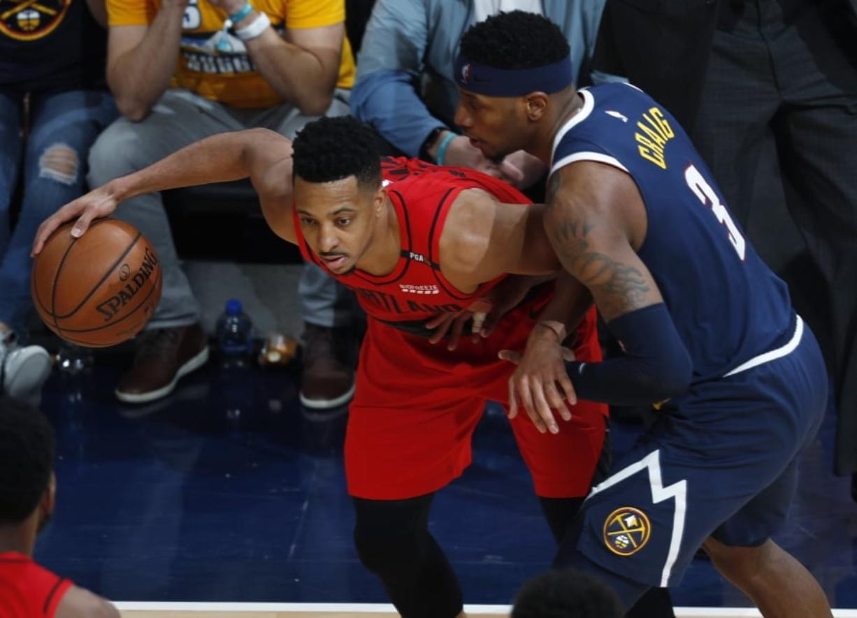 Portland Trail Blazers guard CJ McCollum, left, looks to pass the ball as Denver Nuggets forward Torrey Craig defends in the second half of Game 7 of an NBA basketball second-round playoff series Sunday, May 12, 2019, in Denver. The Trail Blazers won 100-96.
