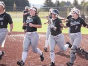 From left to right, Woodland's Olivia Grey, Kailey Christensen, Carleigh Risley and Justice Holcomb run to celebrate Payten Foster's two-run home run Friday at the Ridgefield Outdoor Recreation Complex.