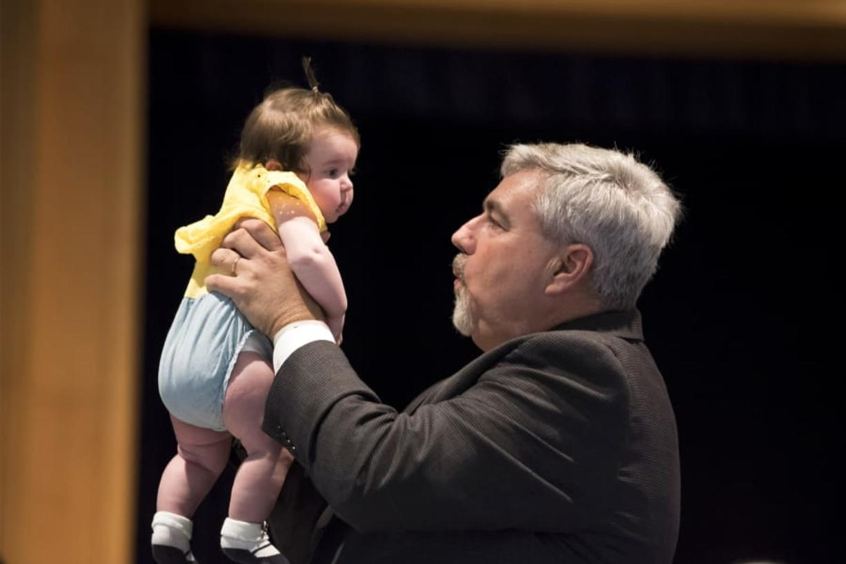 Clark College President Bob Knight holds up his 3-month-old granddaughter, Willow Knight, during his retirement party Thursday afternoon at the Vancouver campus.