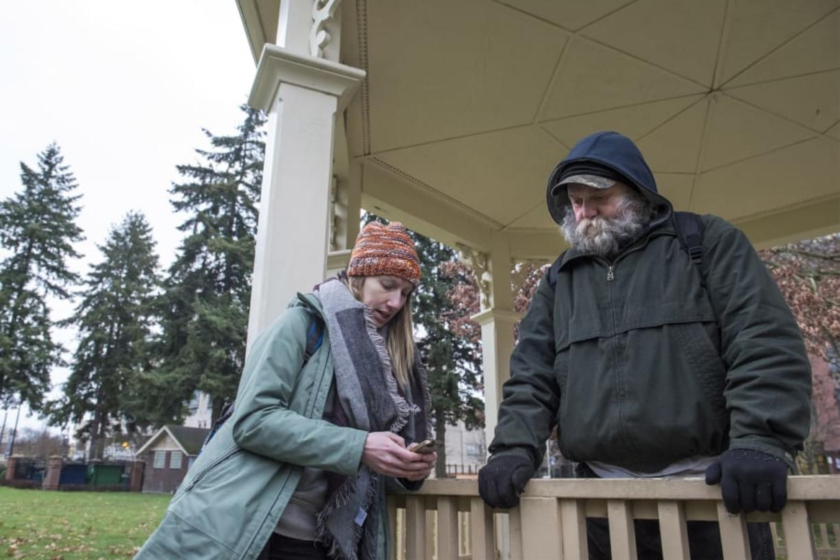 Katelyn Benhoff, lead outreach case manager with Share, left, speaks with a man who declined to give his name while performing the annual Point in Time Count on Jan. 24 in Vancouver's Esther Short Park. Nathan Howard/The Columbian files