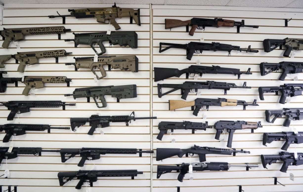 Semi-automatic rifles fill a wall in October at a gun shop in Lynnwood. On Monday, much of Initiative 1639 will go into effect: People wanting to purchase semi-automatic assault rifles will have to undergo an enhanced background check, prove that they've undergone firearms safety training and could face criminal liability for not securing firearms.