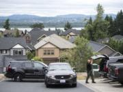 A Clark County Sheriff's Investigator searches his vehicle for gear while investigating a stabbing assault on West Lookout Ridge Drive in Washougal on Tuesday morning, June 18, 2109.