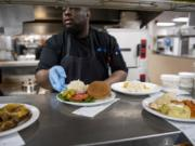 Cook Leadi Cole prepares hot meals for patients at PeaceHealth Southwest Medical Center in Vancouver. The hospital overhauled its menu recently, incorporating new nutrition trends and patient feedback.