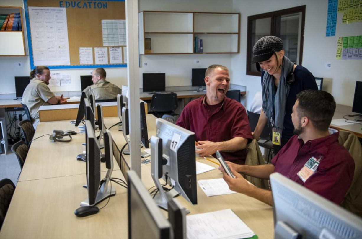 Howard Seaworth, left, and Jakkob McCallin chat with their instructor Lauren Zavrel during her GED class at Larch Corrections Center in Yacolt on May 14. Clark College recently received international recognition for its GED tutoring program at Larch, which pairs inmates preparing to take their tests with trained peer tutors. The program is now certified by the College Reading and Learning Association, which recognizes tutor-training programs across the globe.