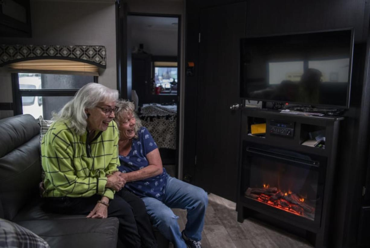 Edith Perrone, left, and her daughter, Glenda Peck, enjoy the electric fireplace in Perrone's new trailer. As rent prices increased, Peck decided to buy a 26-foot recreational vehicle and move into a park. Her mother followed suit a few years later, putting her large family home on the market and purchasing a new 37-foot trailer. Photos by Alisha Jucevic/The Columbian