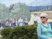 Sharon York looks past a mural of her ancestors, the Wishon family, while talking with her sisters at Orchards Plaza.
