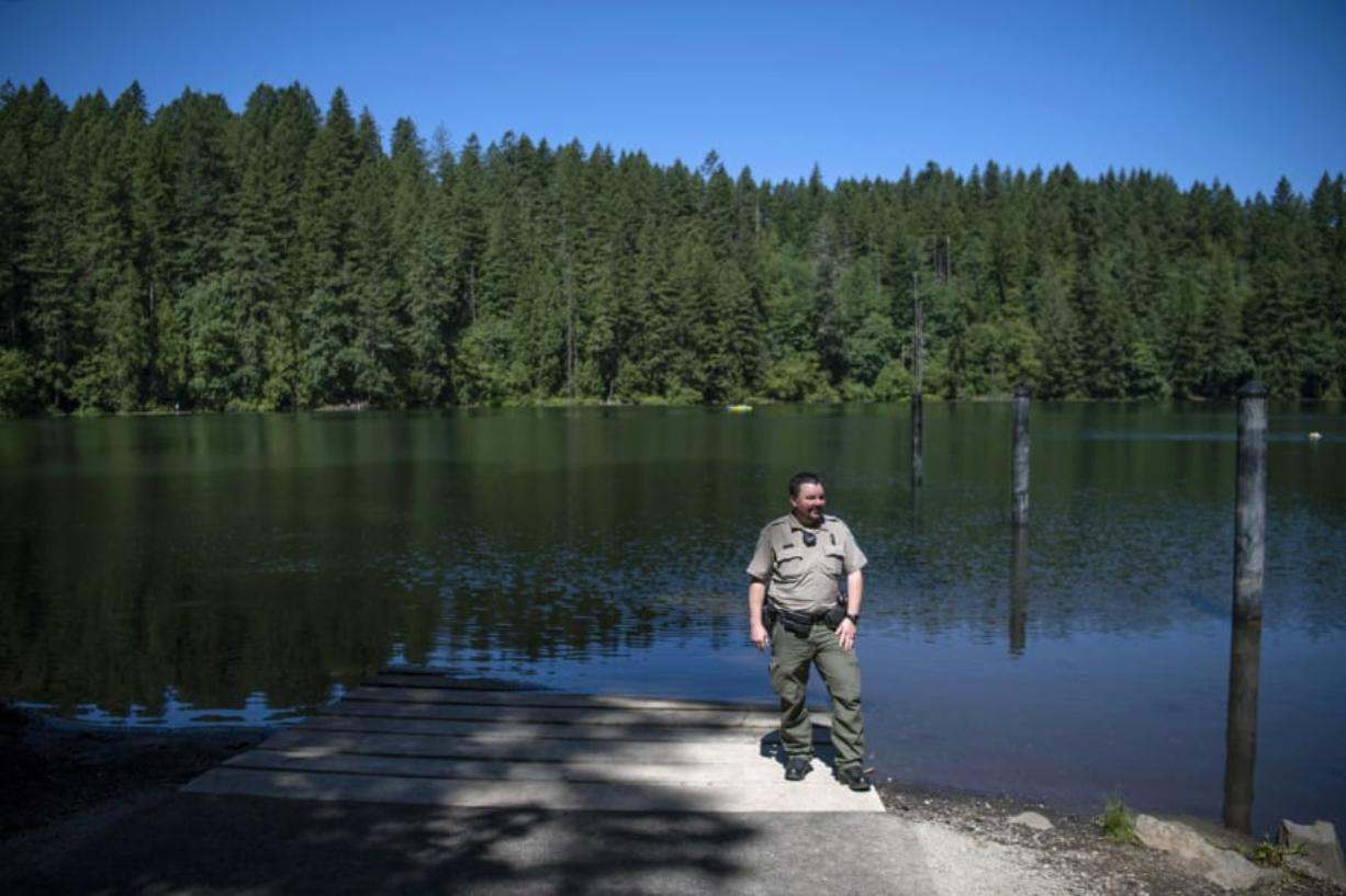 """Washington State Parks Area Manager Heath Yeats oversees Battle Ground Lake State Park, where new projects are on the cusp of completion. Three piles are visible in the water behind Yates that will be used for a new ADA-accessible floating dock that will be installed this month. """"Folks with limited abilities will be able to go out there and fish,"""" Yeats said. """"It's a brand-new feature for this park."""