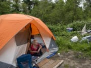 """Christy Jordan, 56, looks out from her tent in a wooded area in Hazel Dell. She says that all the heaps of garbage nearby were left by campers who have since left and that she keeps her trash in a bag nearby. During her three years of being homeless, she's camped out in parks in Vancouver. She says she was once given a 72-hour notice to leave by police and cleared out. """"I listen to the cops; I'm a good girl,"""" she said."""