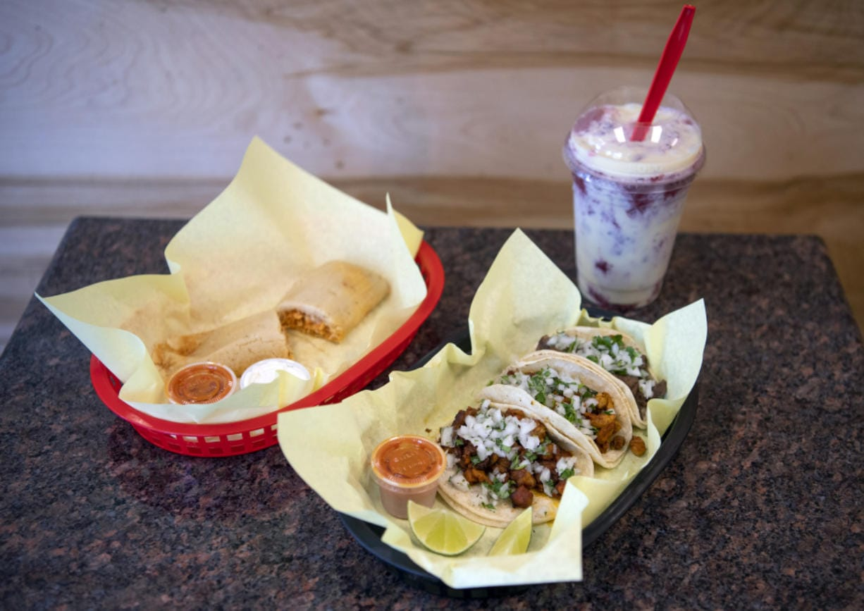A chicken tamale, left, carne asada, pollo, and al pastor tacos, center, and a strawberry Raspados drink, right, are pictured at El Buen Gusto in Vancouver on Friday, June 14, 2019.