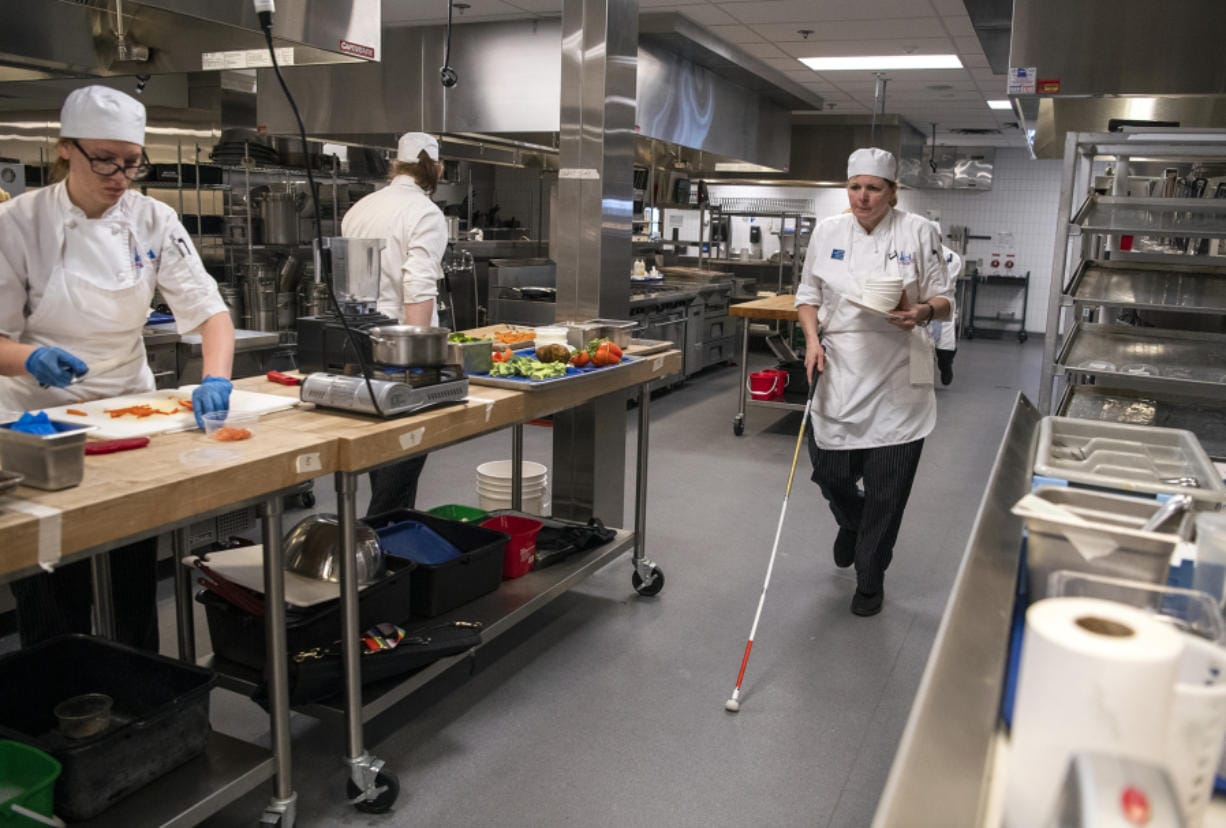Debra Erickson prepared an orange shrimp dish during her culinary arts final exam at Clark College in Vancouver on Wednesday. Erickson has retinitis pigmentosa, a rare genetic disorder that causes the cells in the retina to deteriorate. Erickson hopes to use her new skills to teach blind people how to cook.