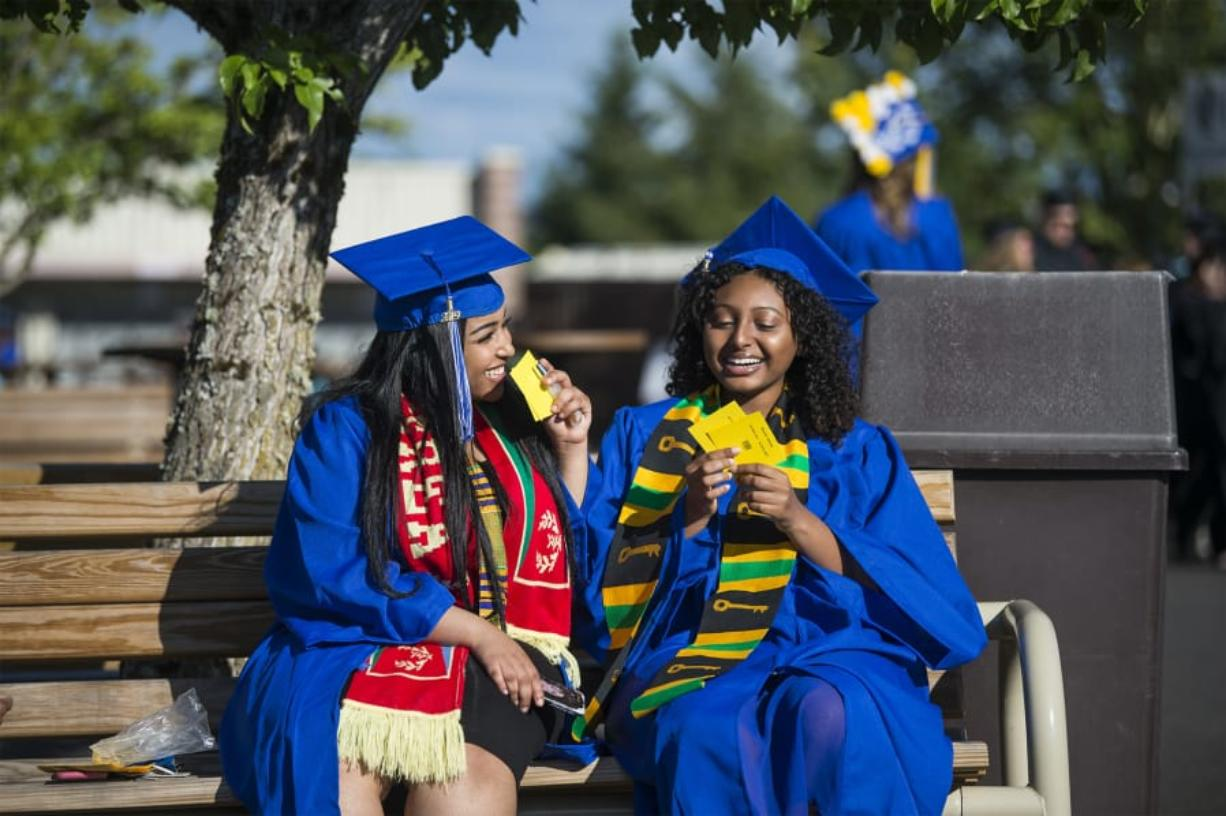 Milkana Ghebretensae, left, and Abesha Kebede share a joke while waiting for the start of the Clark College commencement ceremony at the Sunlight Supply Amphitheater on Thursday night. Both are Running Start students, graduating with both their associate degrees and their high school degrees.