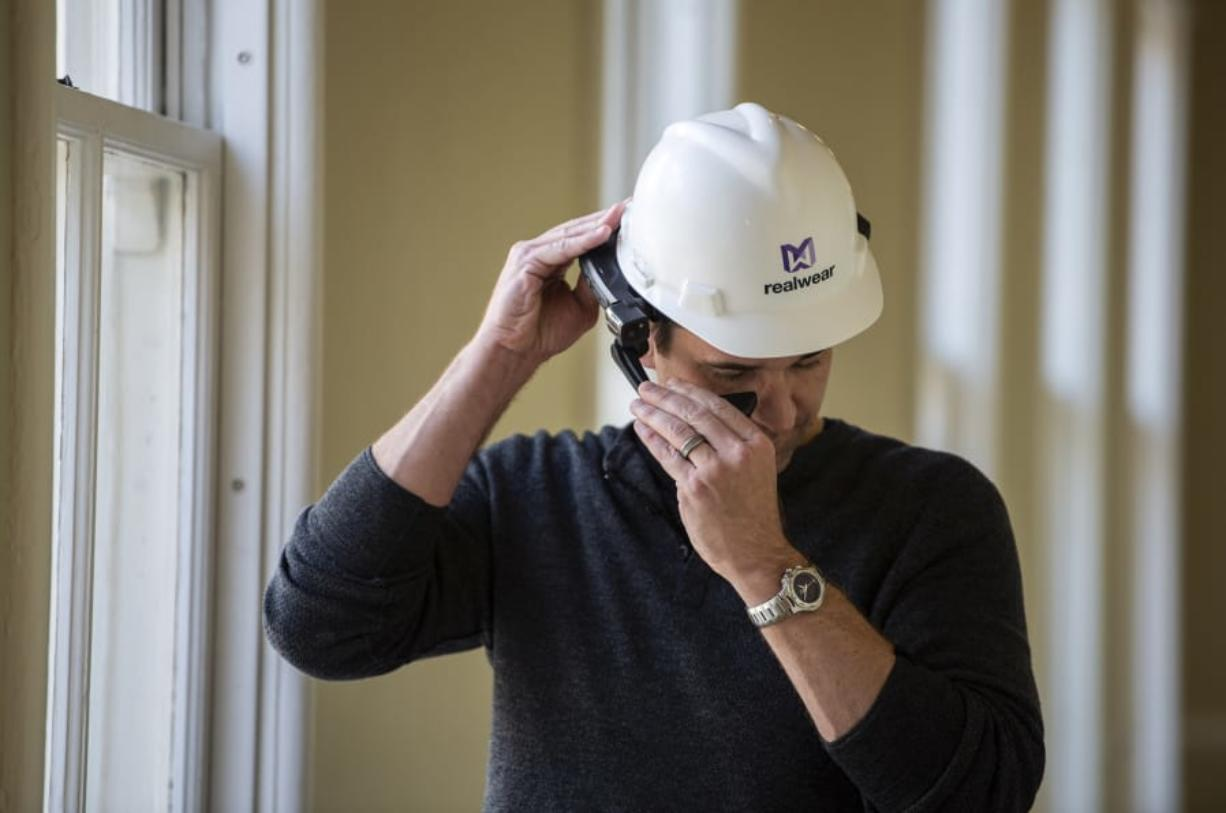 RealWear CEO Andy Lowery adjusts one of the company's HMT-1 headsets, a hands-free Android computer system for industrial workers, at the RealWear headquarters in Vancouver on Friday. The company announced that it has secured $80 million in a new funding round.