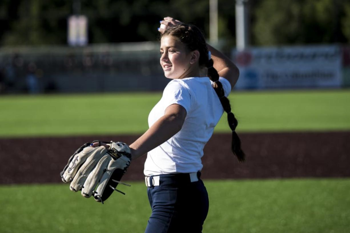Elizabeth Peery throws out the first pitch at the Ridgefield Raptors game Friday, where she was honored for making the finals of the national Pitch, Hit & Run competition.