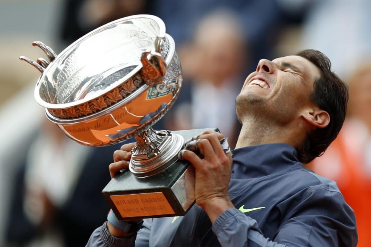 Spain's Rafael Nadal lifts the cup after defeating Austria's Dominic Thiem in their men's final match of the French Open tennis tournament at the Roland Garros stadium in Paris, Sunday, June 9, 2019. Nadal won 6-3, 5-7, 6-1, 6-1.