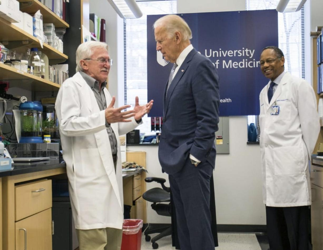 FILE - In this Feb. 10, 2016 file photo, Vice President Joe Biden speaks with Nobel Laureate Dr. Paul Modrich, left, as Dr. A. Eugene Washington, Chancellor for Health Affairs at Duke University, right listens in a laboratory at Duke University School of Medicine in Durham, N.C. Biden's defining venture since leaving the Obama White House is the Biden Cancer Initiative, a nonprofit aimed at speeding a cancer cure in memory of his son.