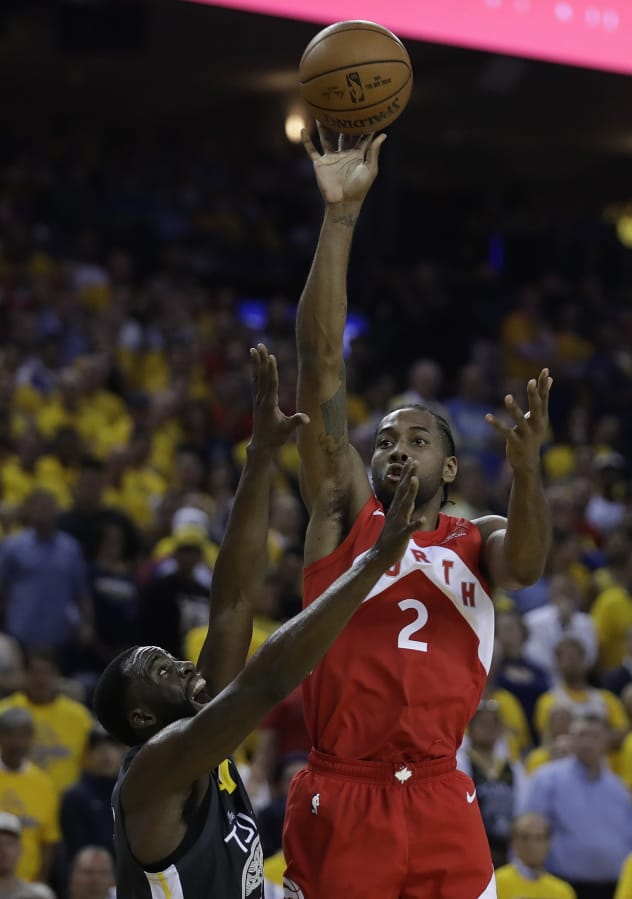 c2f769f583b Toronto Raptors' Kawhi Leonard, right, shoots over Golden State Warriors'  Draymond Green