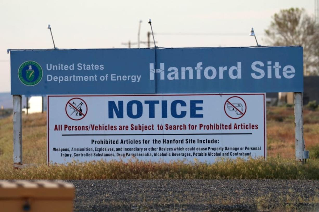 FILE - In this May 9, 2017 file photo, signs are posted near the entrance to the Hanford Nuclear Reservation in Richland, Wash. A federal judge on Thursday, June 13, 2019 rejected the Trump administration's challenge to a Washington state law that makes it easier for former workers at the Hanford Nuclear Reservation to win workers compensation benefits.