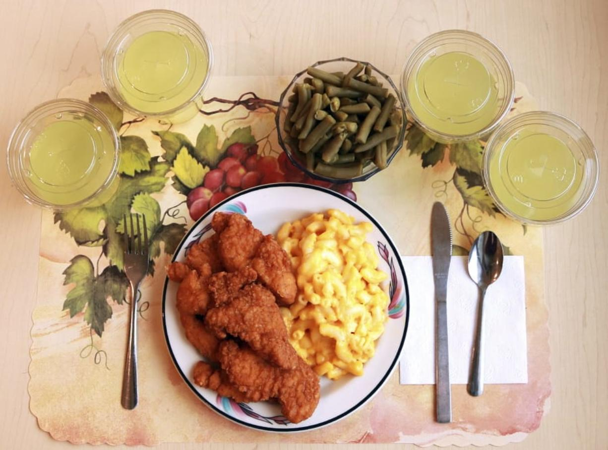 """This undated photo provided by the National Institutes of Health in June 2019 shows an """"ultra-processed"""" lunch including brand name macaroni and cheese, chicken tenders, canned green beans and diet lemonade. Researchers found people ate an average of 500 extra calories a day when fed mostly processed foods, compared with when the same people were fed minimally processed foods. That's even though researchers tried to match the meals for nutrients like fat, fiber and sugar."""