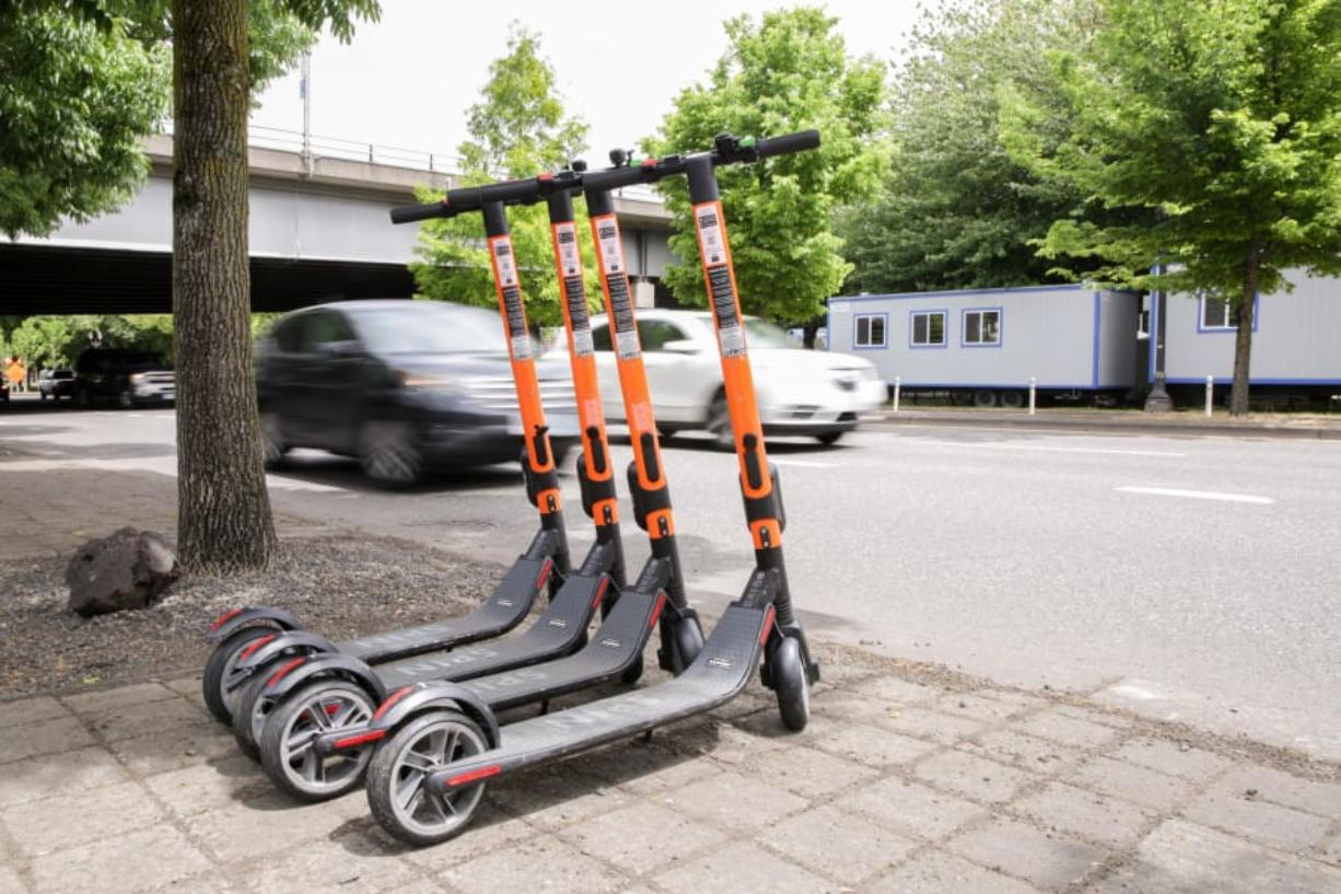 Commuters pass by a row of parked SPIN electric scooters May 17 on Southwest Naito Parkway in downtown Portland.  (Bryan M.