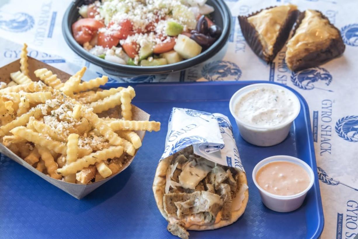 Greek fries, from left, Greek salad, Gyreuben, and a slice of baklava at The Gyro Shack. Nathan Howard/The Columbian