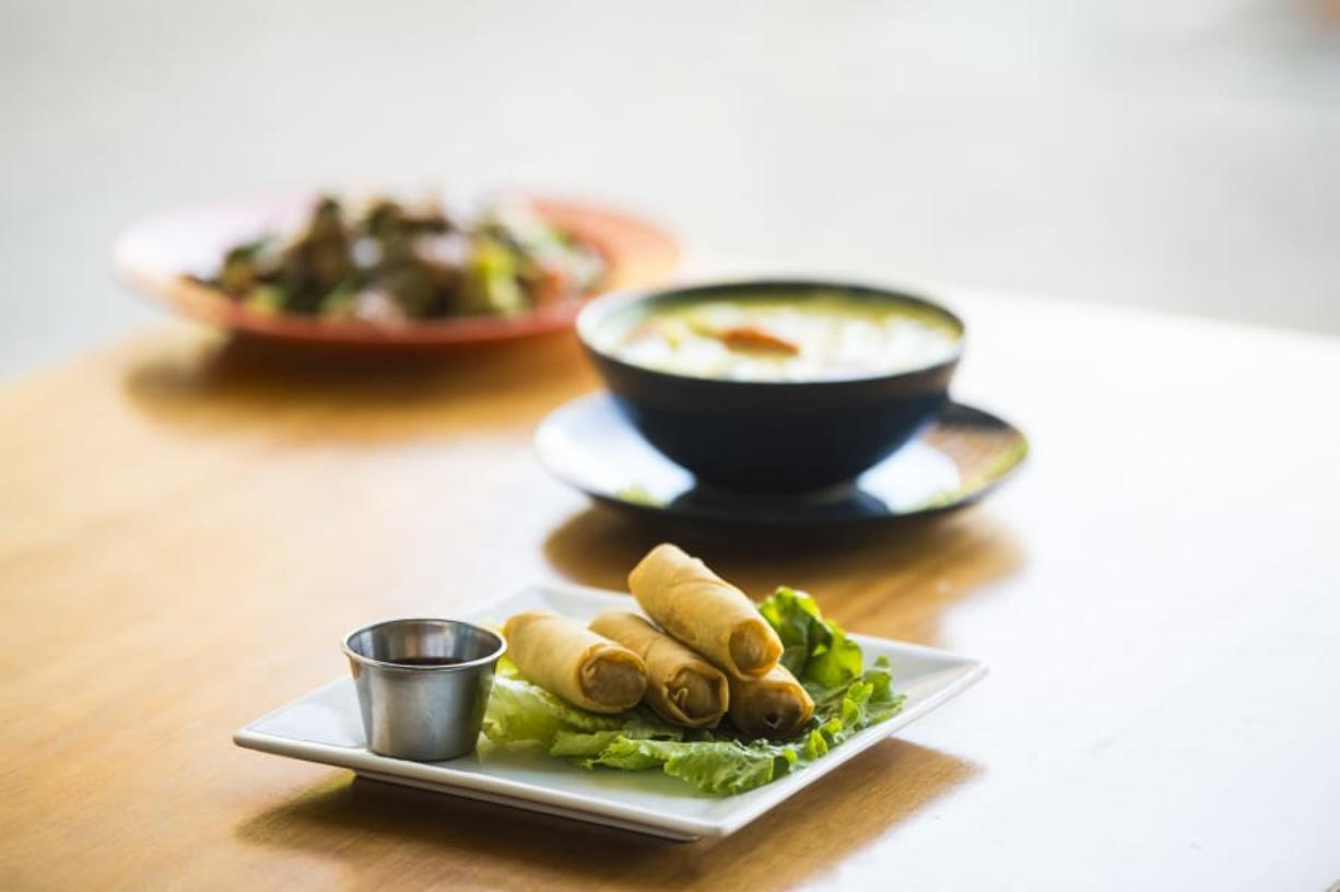 Fried spring rolls, front to back, Yellow Curry with Chicken, and Pra Ram with Beef is seen here at Nom Nom Restaurant and Grill in Vancouver on Tuesday, June 18, 2109. (Nathan Howard/The Columbian)