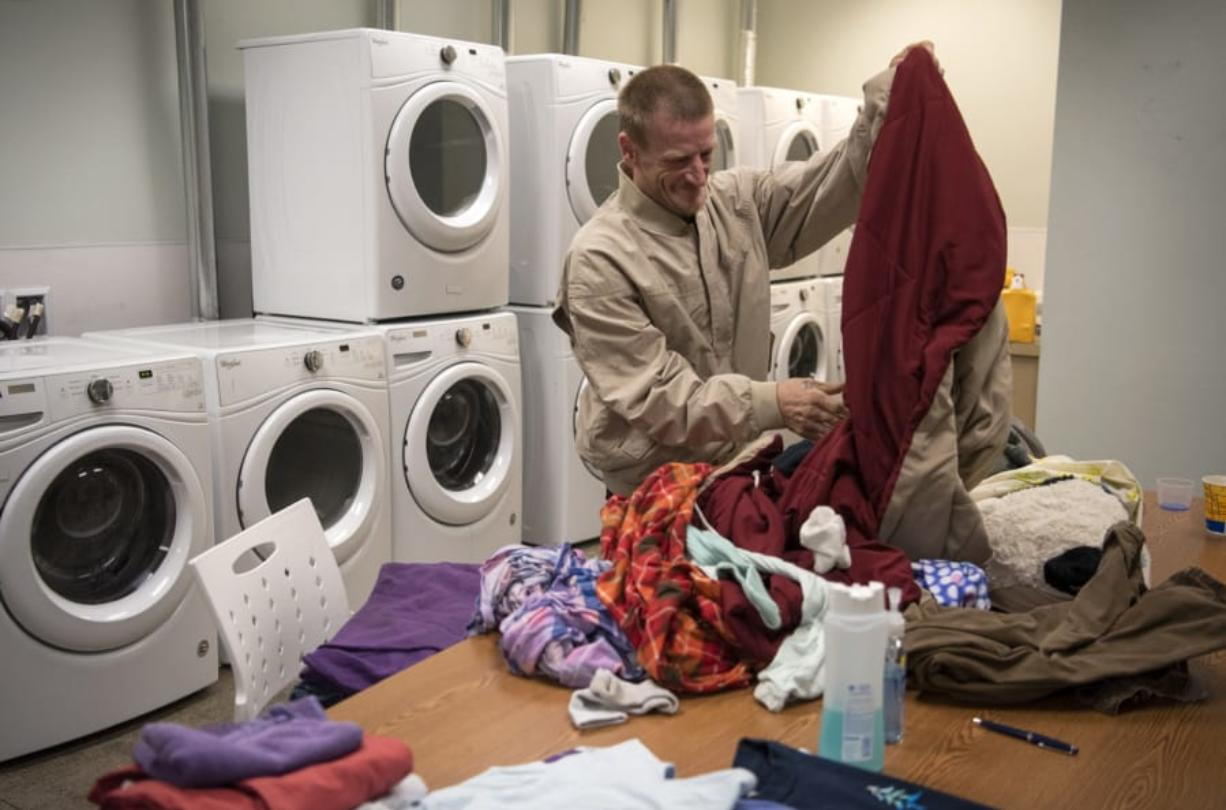 """Robert Thompson folds laundry at the Vancouver Navigation Center on June 27. Laundry is one of the most used services. Thompson lives out of his car with his partner, and they come to the day center every day. """"They're doing really good here,"""" he said."""