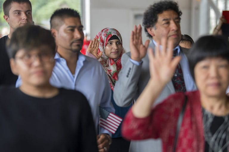 Jalilah Alzyadi, center, who is originally from Yemen but now lives in Vancouver, joins fellow candidates for citizenship as they take the oath of allegiance during the Special Naturalization Ceremony at the Pearson Air Museum's historic hangar Wednesday afternoon, July 3, 2019. 39 people from 19 different countries became American citizens during the ceremony, which included patriotic music and a celebratory cake.