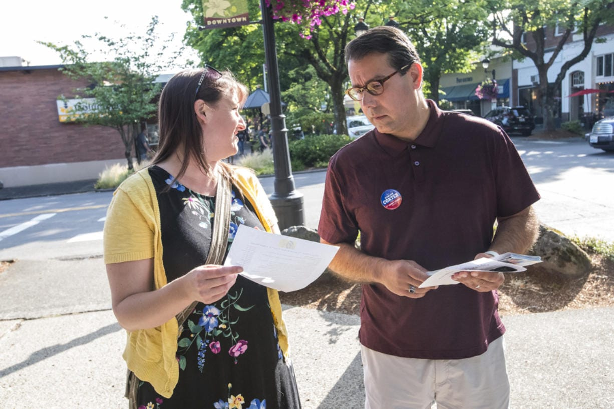 Clark County Council candidate Adrian Cortes and his campaign coordinator, Wendy Cleveland, consult a list of businesses they planned to visit while campaigning during a recent Camas First Friday event.