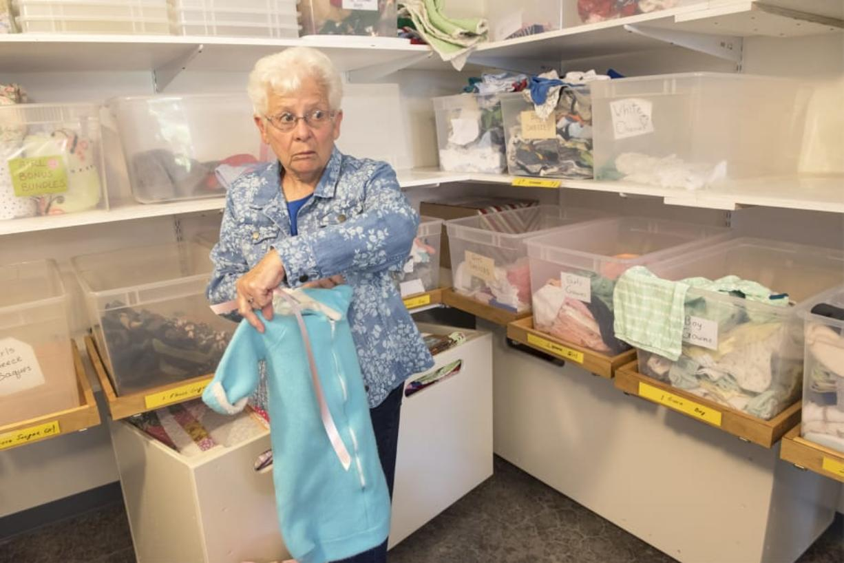 Volunteer Bonnie Bachle holds up a blue fleece sleeping sack, currently one of the most-needed newborn items at Babies in Need.