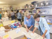 Volunteers Judy Walter, left, and Shirley Brandenburg with Babies in Need build layettes at All Saints Episcopal Church in Hazel Dell. Walter said she's been volunteering with the group since the early 2000s.