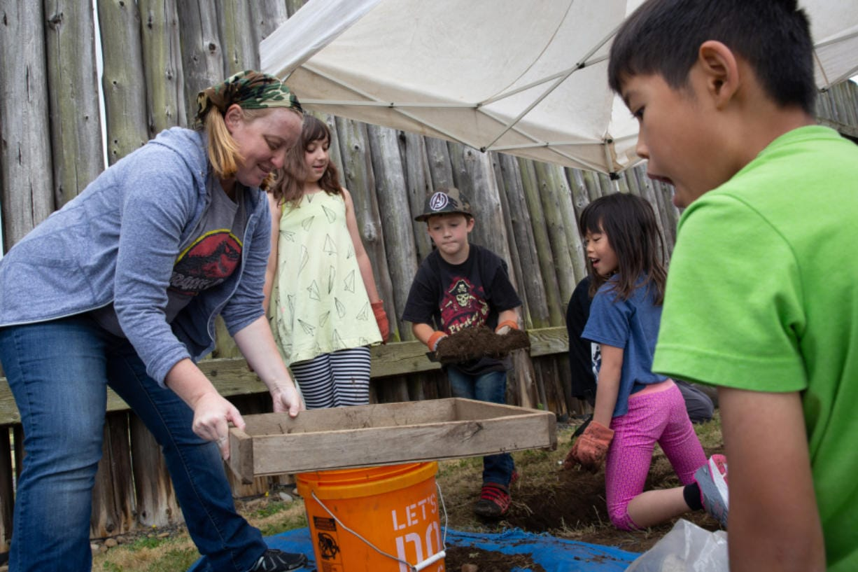 Volunteer Erin Miermans, from left, Evelynn Ramsay, 8, of Vancouver, Rhonin Parks, 8, of Vancouver, Kaitlyn Chan, 6, and her brother, Emlyn Chan, 10, both of Redmond, watch as dirt from the mock archeological dig is sifted Saturday at Fort Vancouver National Historic Site.