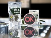 An OK Cannabis sign is displayed with marijuana products at Main Street Marijuana in Vancouver. The industry-led program randomly pulls products from store shelves to test for pesticides and other contaminants.