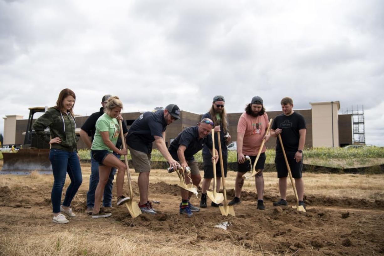 The Trap Door team pours beer out onto the golden shovels during the groundbreaking ceremony at the site of Pioneer Village in Ridgefield. Trap Door was the first tenant to sign a lease at the mixed-use development, which will also include about 300 apartments.