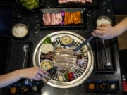 Pork belly, baby octopus, corn and veggie skewers are placed on the grill to cook at KingKong Korean BBQ in Vancouver.