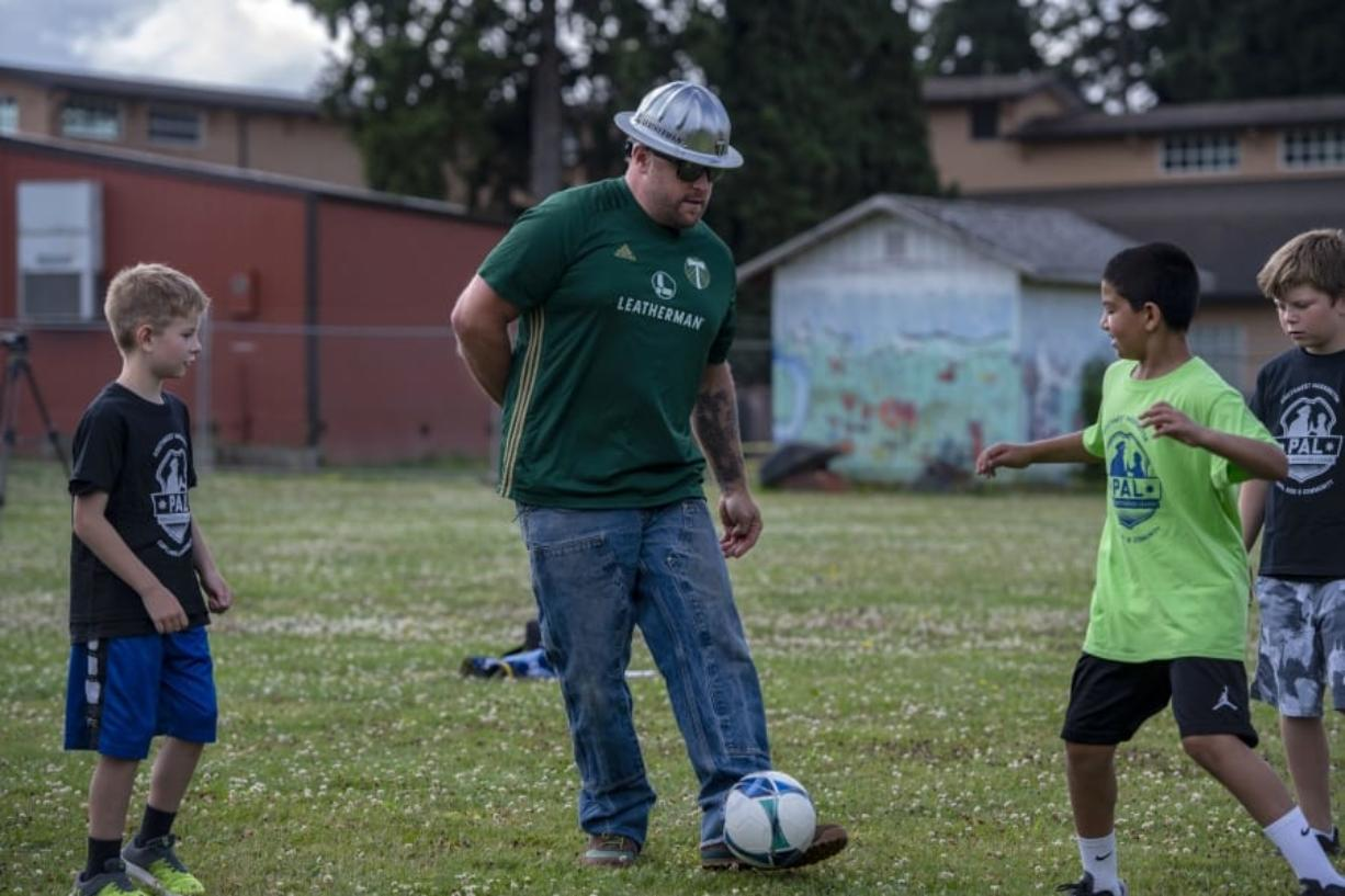 Julian Charbonneau, from left, Portland Timbers mascot Joey Webber, also known as Timber Joey, with Ezequiel Valencia and Chase Anderson, kick the ball around during a game of keep away Thursday morning at Fruit Valley Elementary School.