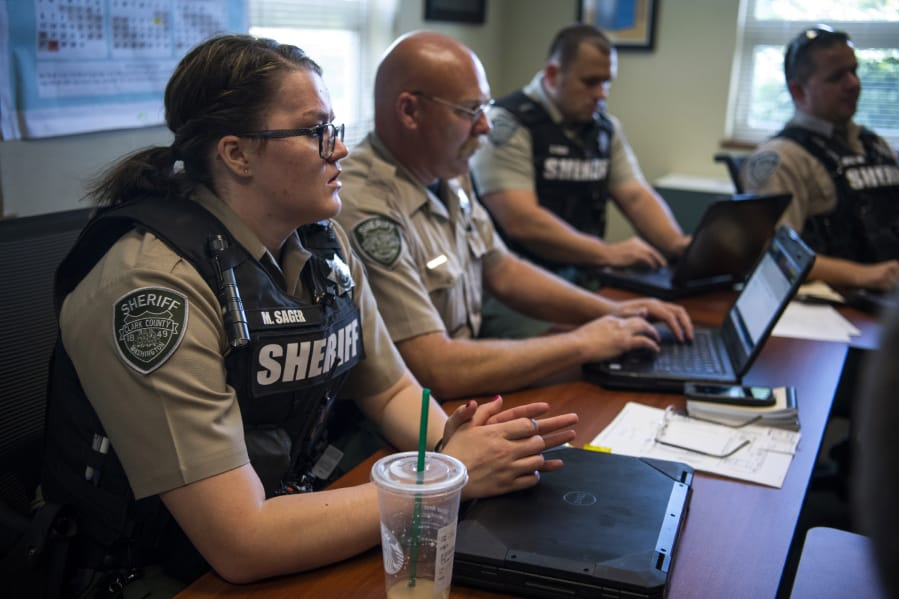 Deputy Melissa Sager and her fellow deputies meet for an afternoon debriefing at the Clark County Sheriff's West Precinct in Ridgefield on July 18.
