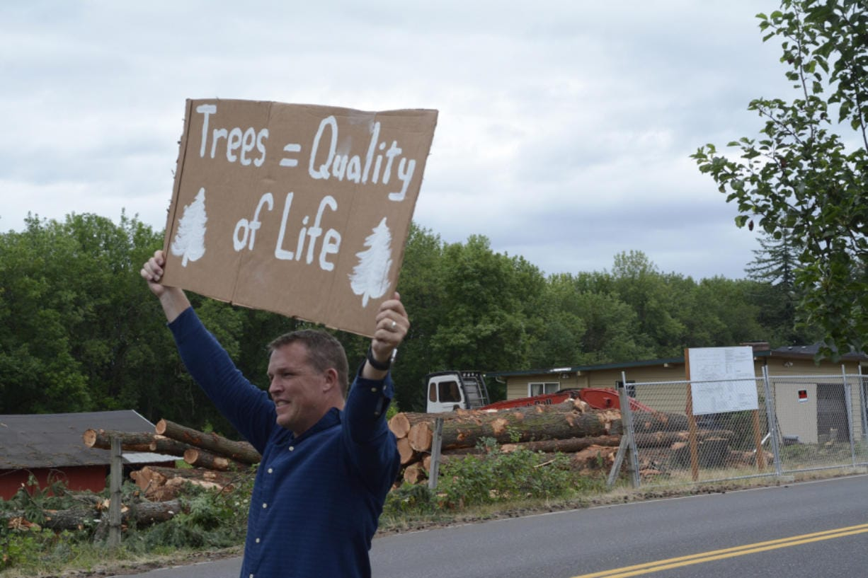 Mike King holds up a sign along Northwest 43rd Avenue in Camas on Wednesday during a protest by the Camas Tree Protectors. The new group hosted the event to protest a developer cutting down nearly 80 trees, some of which can be seen across the street. (Adam Littman/The Columbian)