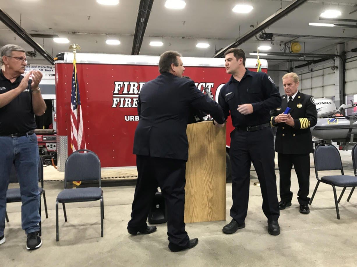 Clark County Fire District 6 Firefighter Tony Lothspeich prepares to receive an award from Board of Fire Commissioners Chair Casey Collins on Tuesday at Station 61 in Hazel Dell.