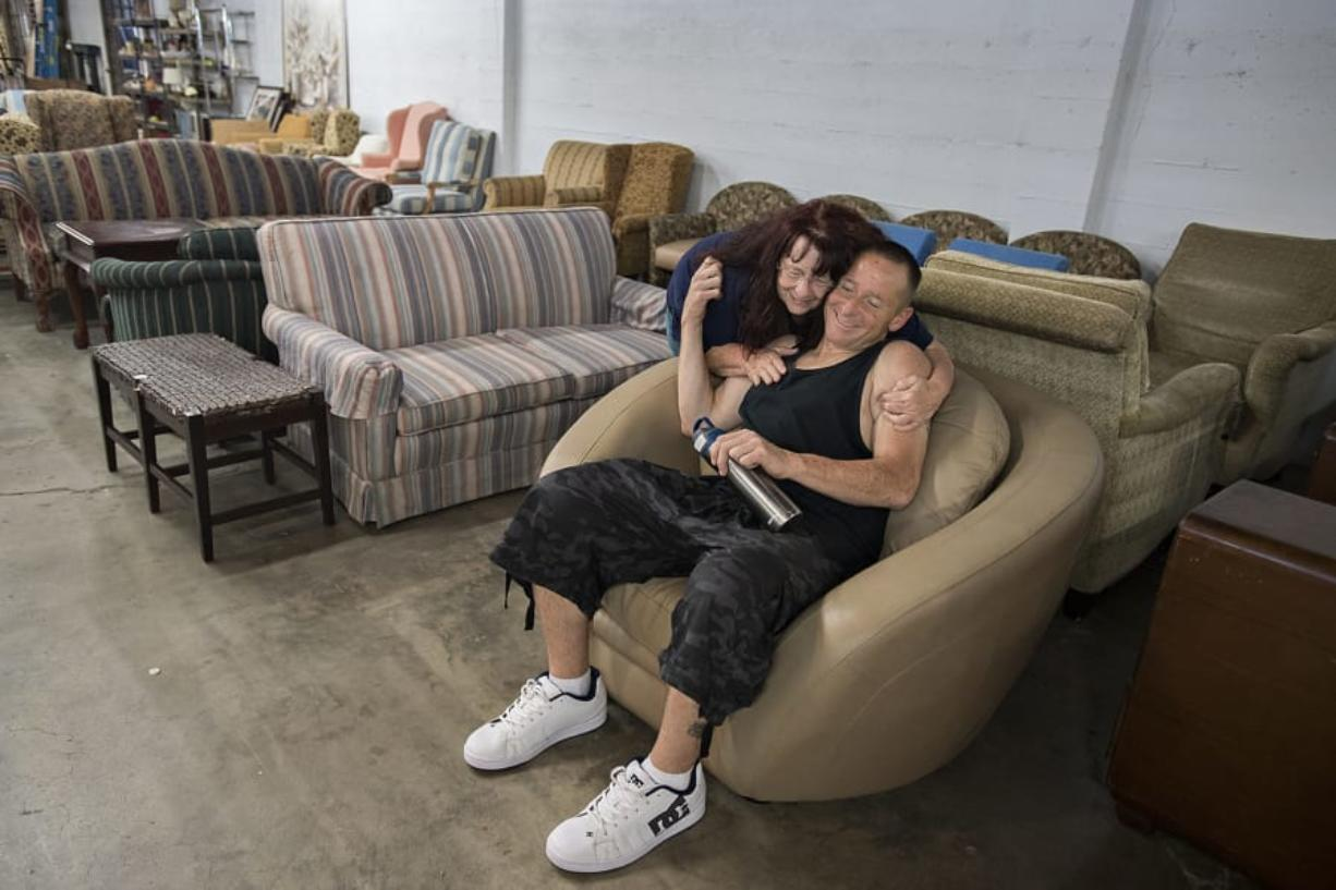 Marsha Barley, 69, embraces her son, Lance, 43, while shopping for furniture at NW Furniture Bank on Friday. The Barleys were living in their van until they recently got housing through the Vancouver Navigation Center. People can shop for all the furniture they need for $75 at NW Furniture Bank.