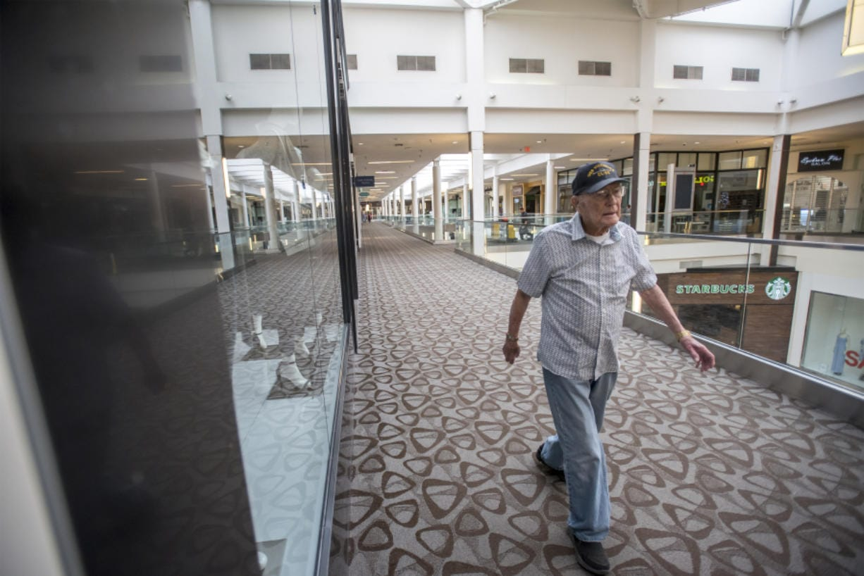 Carl Lingenfelter, a World War II veteran who will turn 100 on Monday, completes a lap of Vancouver Mall during his daily walk through the mall, which unlocks its doors for walkers long before stores open to shoppers.