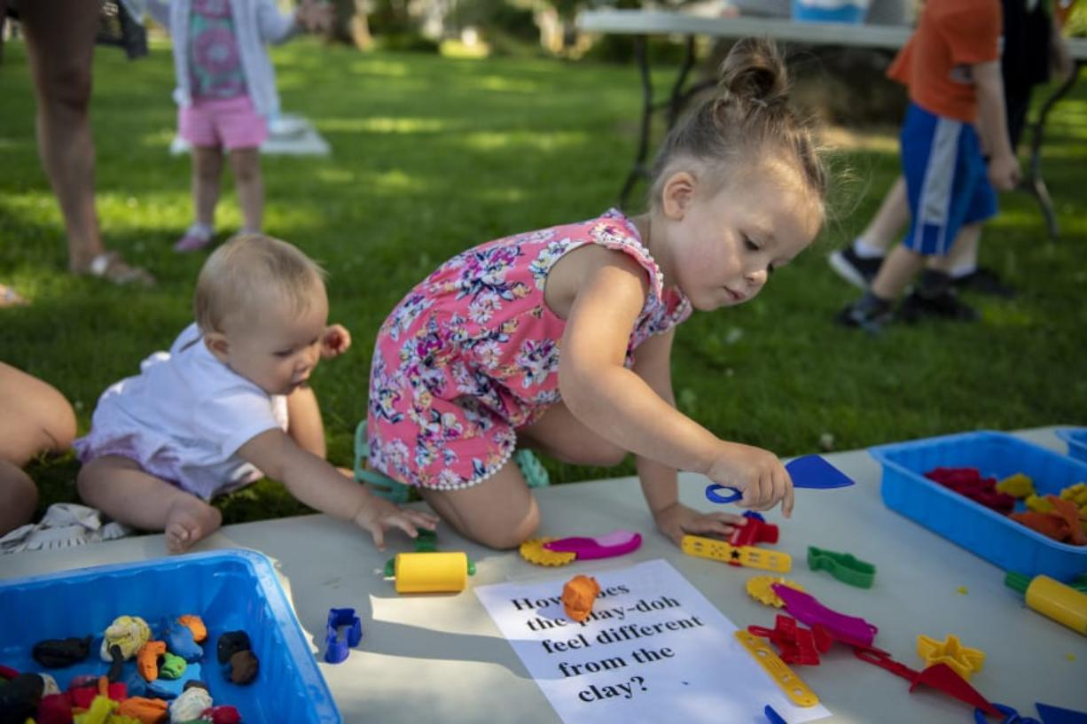 Nine-month-old Haddie Gordon, left, and sister Willow, 3, amuse themselves with Play-Doh on Thursday morning outside the Woodland Community Library during its Sensory Play in the Park event. Library staffers hope they will be able to host more activities for kids and families once the Fort Vancouver Regional Library District raises enough money to construct a bigger building in Woodland. Zach Wilkinson/The Columbian