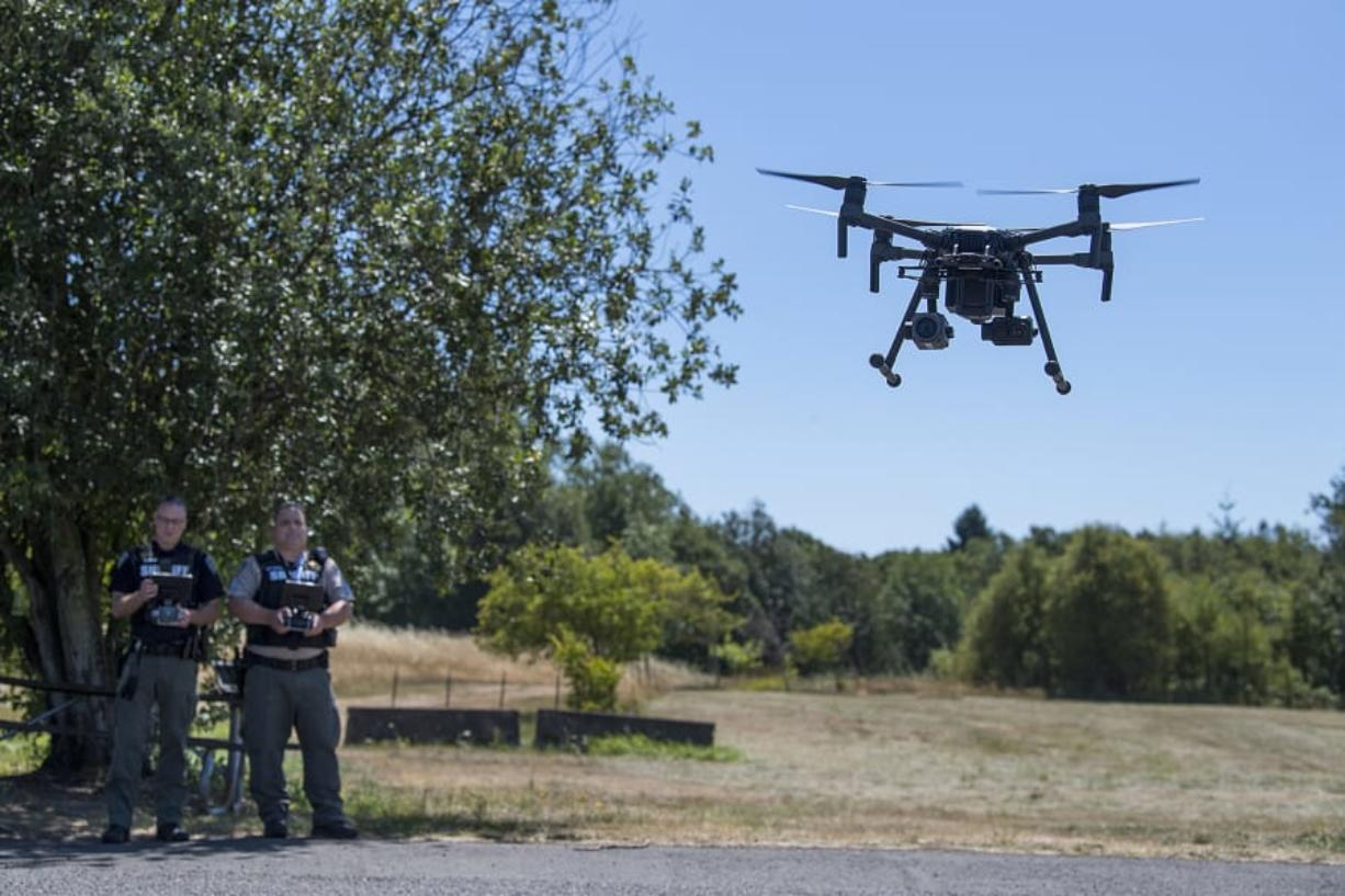 Detective Todd Young, left, and Sgt. Jason Granneman demonstrate one of the drones they use while working in the field at the Clark County Sheriff's Office's West Precinct.