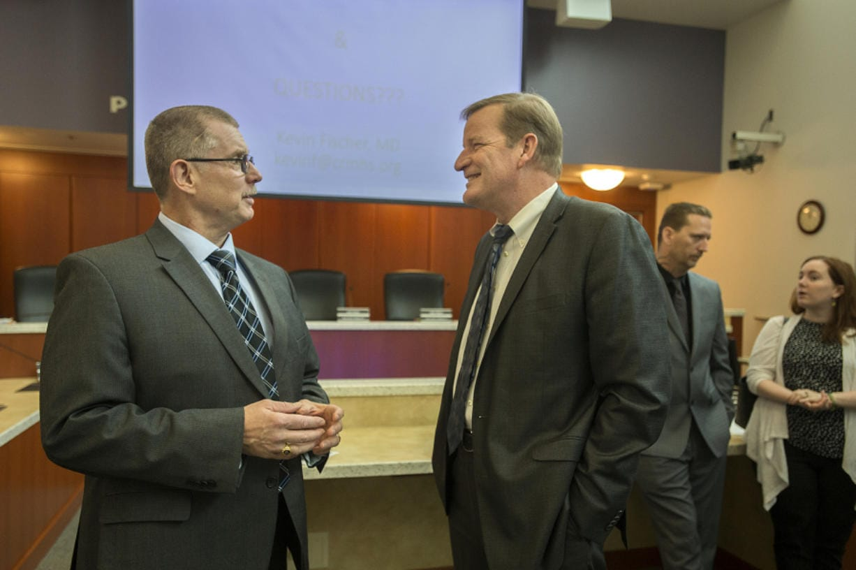 Chief Ric Bishop of the Clark County Jail, left, chats with Craig Pridemore, CEO of Columbia River Mental Health Services, following a meeting Thursday morning at the Clark County Public Service Center. The jail is partnering with the nonprofit to expand opioid treatment in the jail.