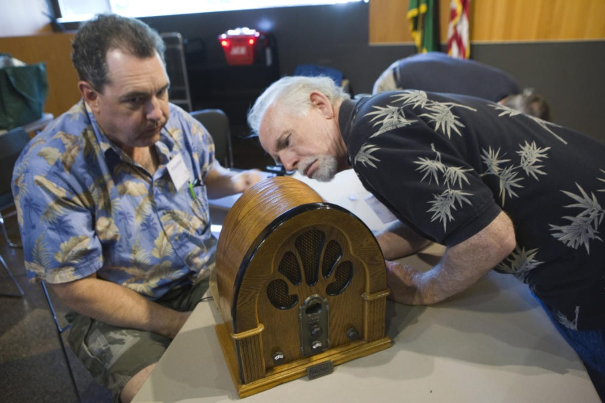Volunteers Neil Sedell and Dave Meigs look at an old radio as they attempt to repair it during a 2017 event at the Vancouver Community Library.