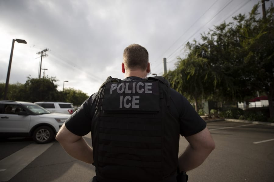 A U.S. Immigration and Customs Enforcement officer looks on during an operation July 8 in Escondido, Calif. Associated Press files
